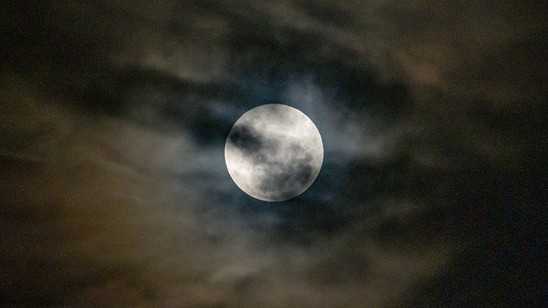 Full supermoon rising through the clouds.